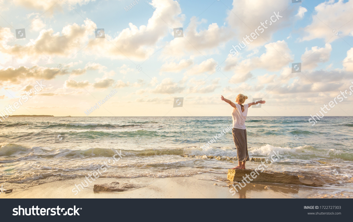 Relaxed woman enjoying sun, freedom and life an beautiful beach in sunset. Young lady feeling free, relaxed and happy. Concept of vacations, freedom, happiness, enjoyment and well being. #1722727303