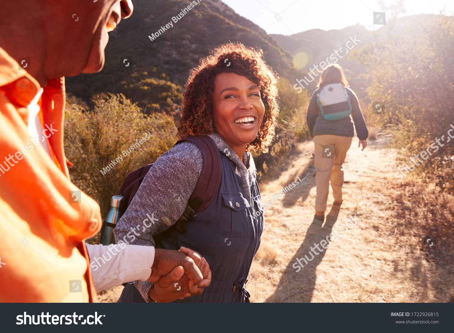 Woman Helping Man On Trail As Group Of Senior Friends Go Hiking In Countryside Together #1722926815