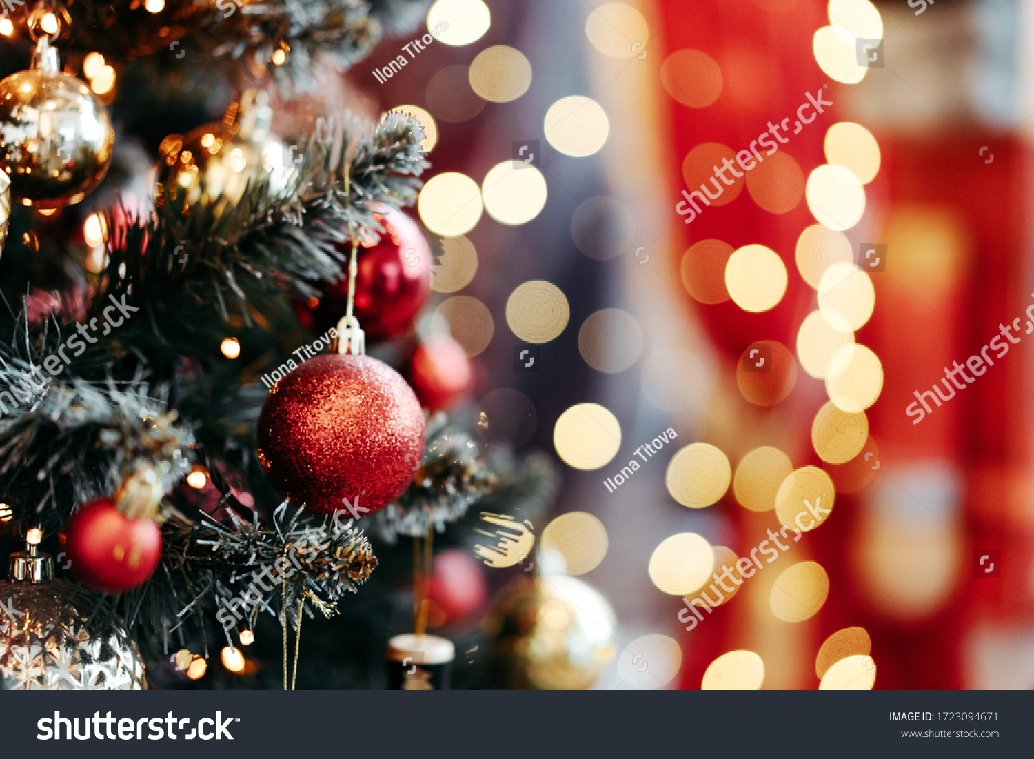 Close up of balls on christmas tree. Bokeh garlands in the background. New Year concept. #1723094671
