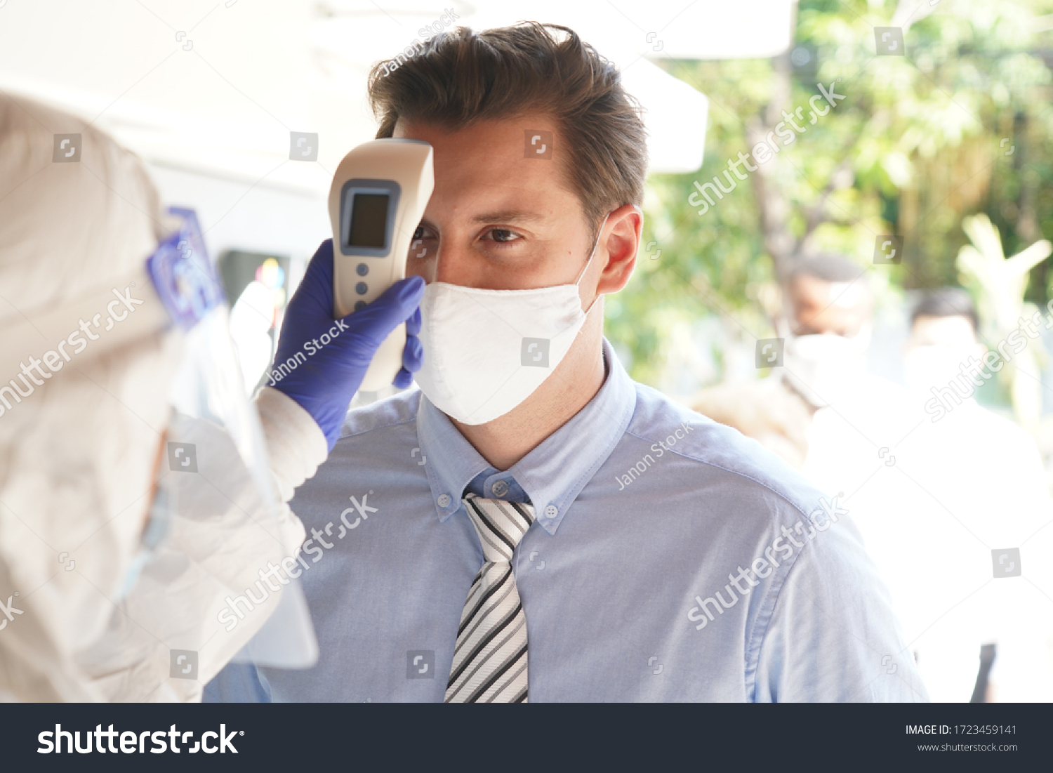 Disease control experts  use an Infrared thermometer equipment to check the temperature on the forehead and use alcohol gel to screen the patients addicted to Covid before entering the building. #1723459141