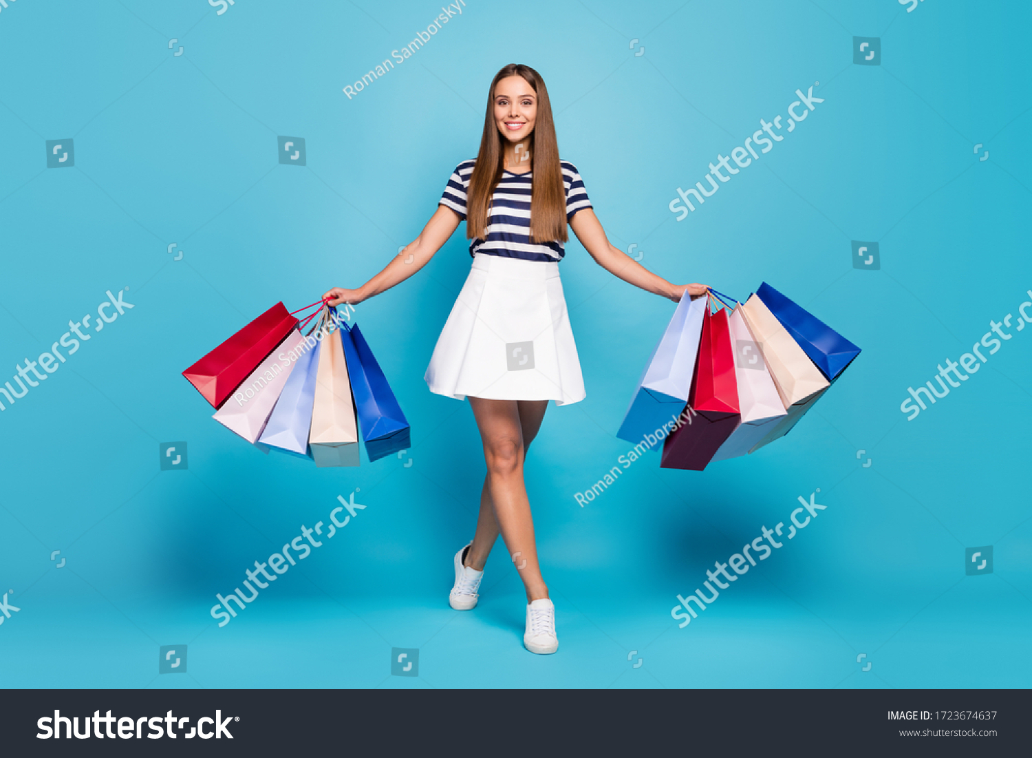 Full body photo of charming funny lady tourist walk shopping center carry many packs good mood best weekend wear white striped t-shirt skirt shoes isolated blue background #1723674637