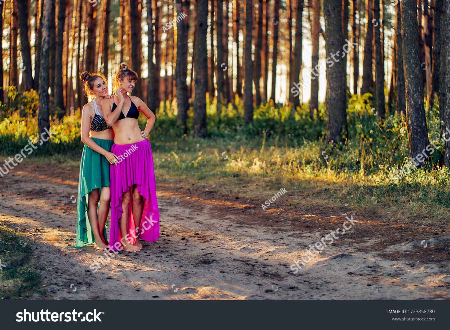 https://image.shutterstock.com/z/stock-photo-two-girls-in-bathing-suits-and-long-dresses-in-the-forest-at-sunset-1723858780.jpg