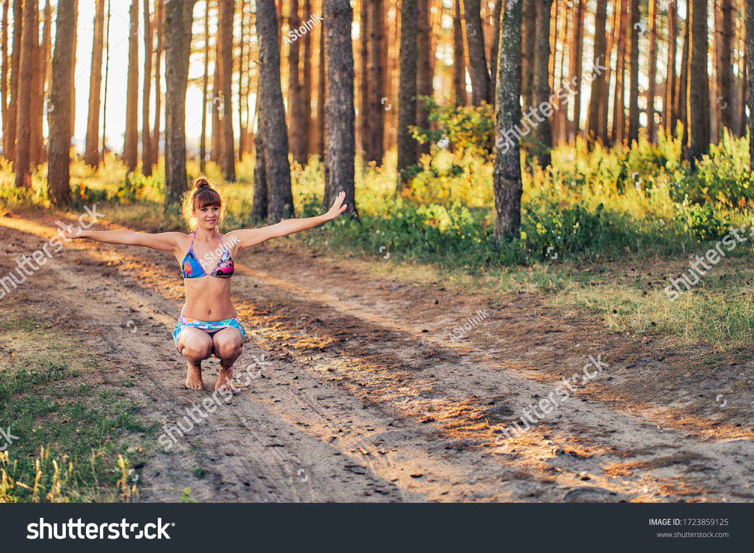 https://image.shutterstock.com/z/stock-photo-girl-in-a-bathing-suit-and-short-skirt-is-training-in-the-forest-1723859125.jpg