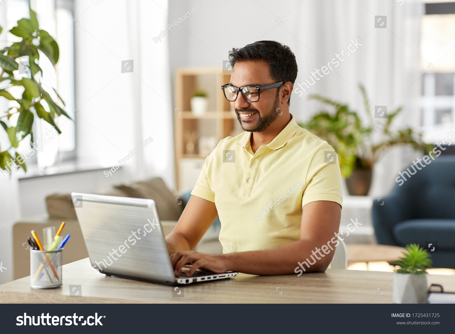 technology, remote job and lifestyle concept - happy indian man in glasses with laptop computer working at home office #1725431725