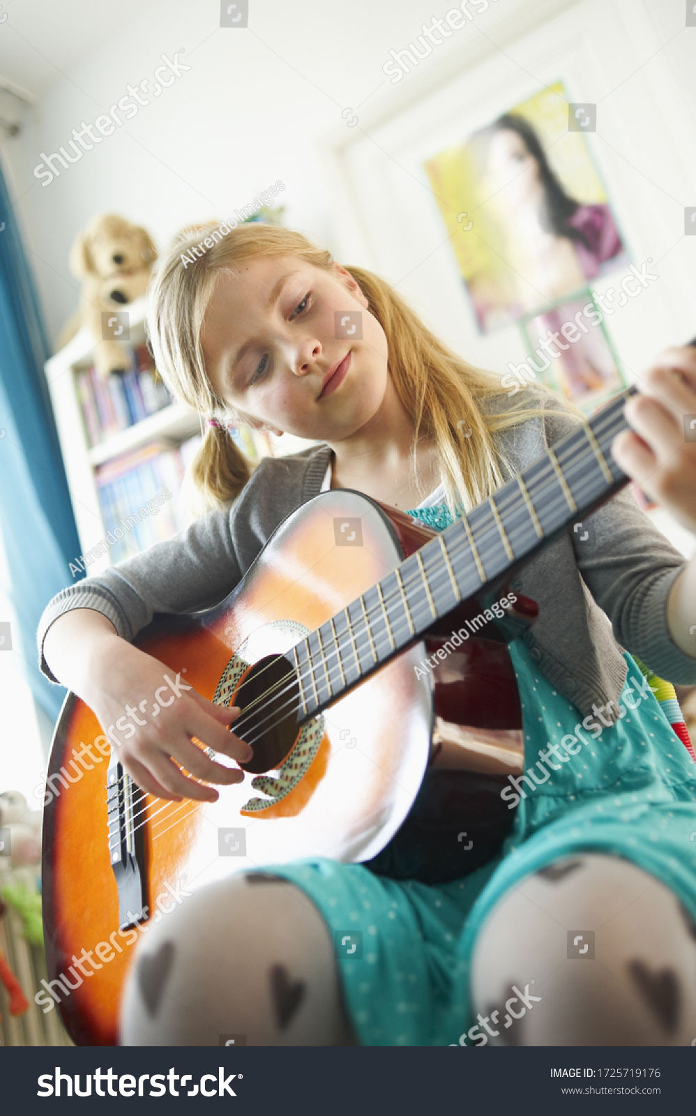 Young girl playing guitar in bedroom #1725719176