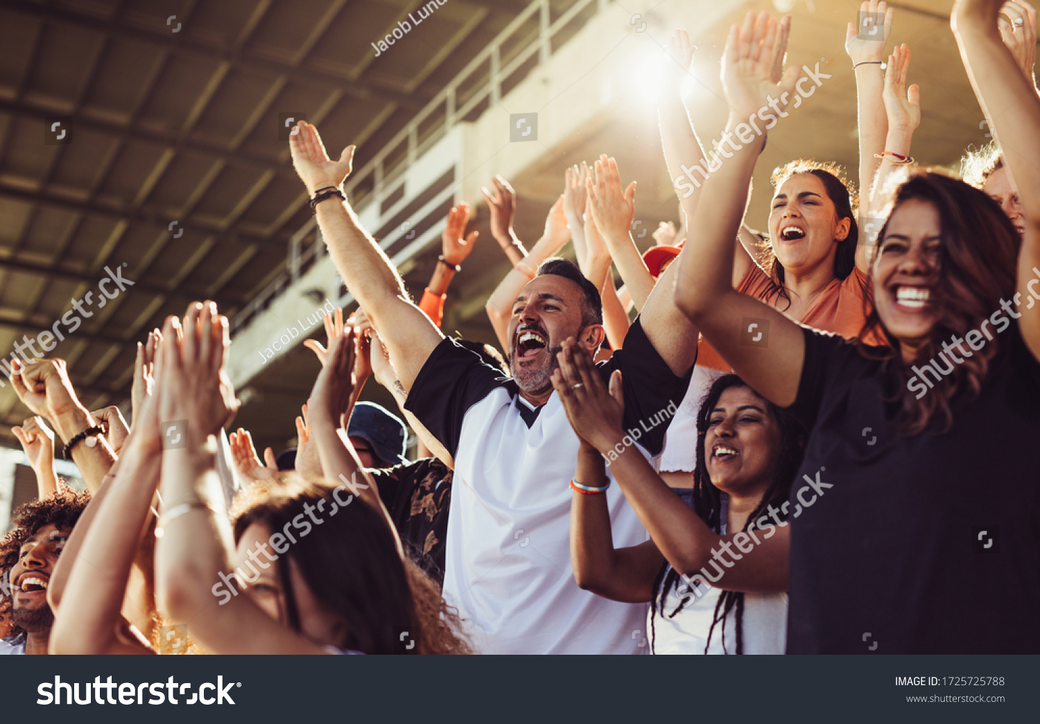 Crowd of sports fans cheering during a match in stadium. Excited people standing with their arms raised, clapping and yelling to encourage their team. #1725725788