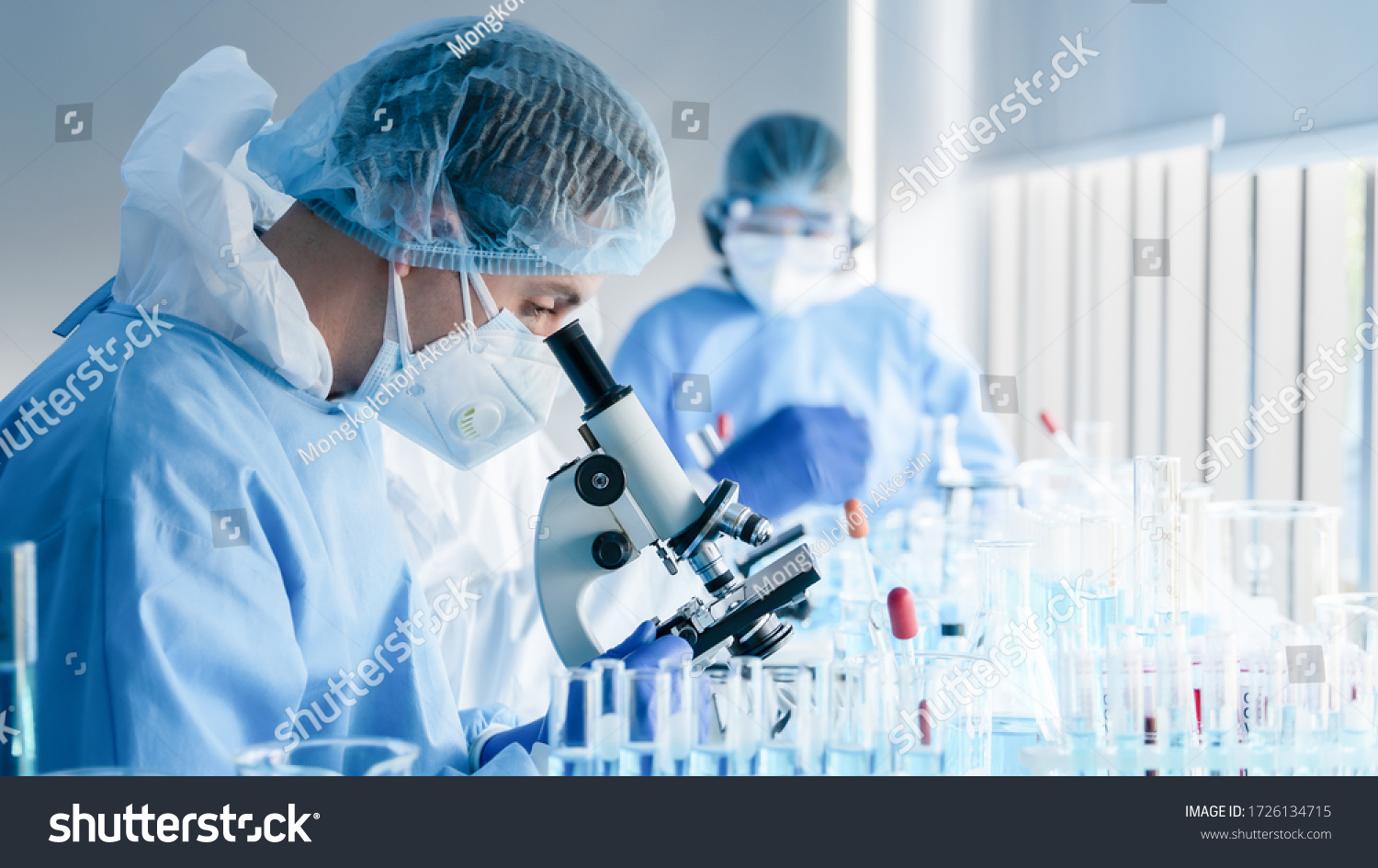 biochemical research scientist team working with microscope for coronavirus vaccine development in pharmaceutical research labolatory, selective focus #1726134715