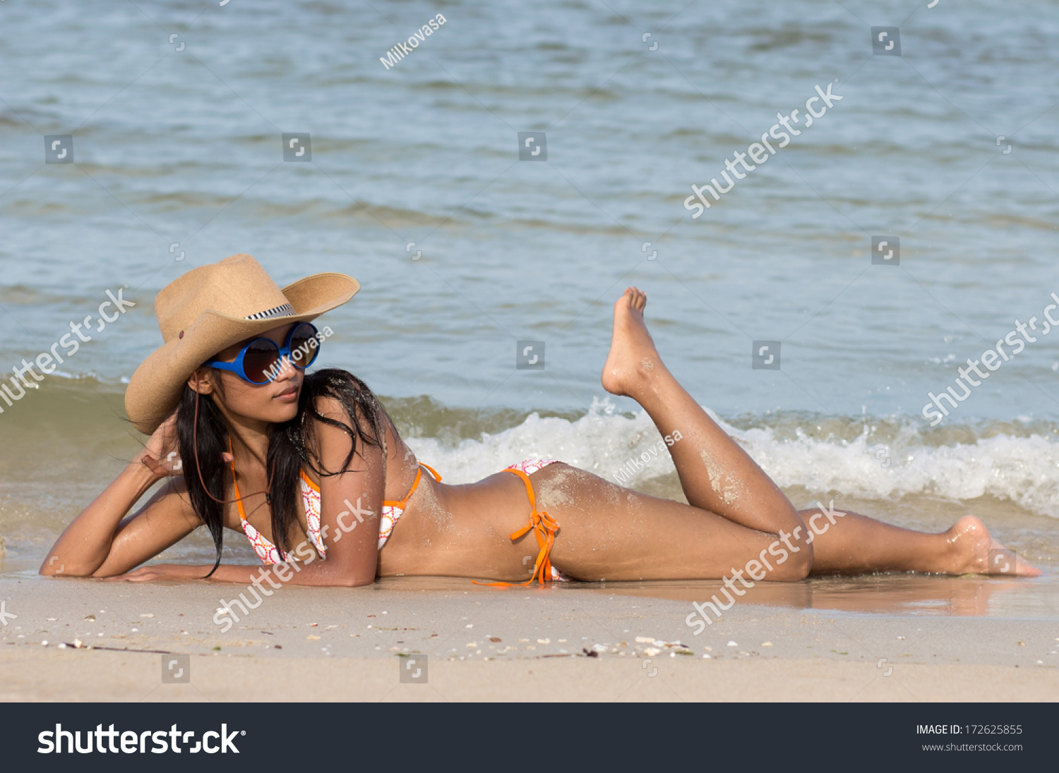 19d3ea855142f Attractive girl on seashore. Young woman with a cowboy hat lying on a sea  beach