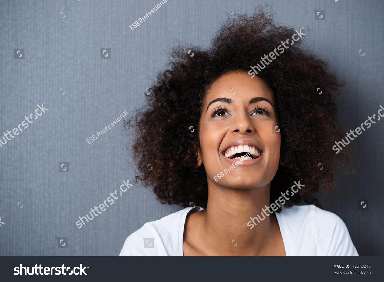 笑非裔美国妇女与一个黑人的发型和良好的幽默感微笑着她的头倾斜回看向空中