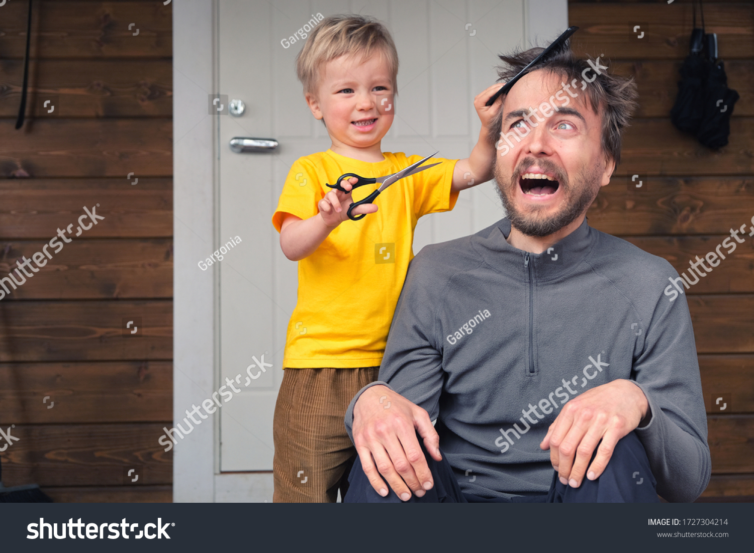 Funny child cutting hair to his father at home during quarantine lockdown. Little hairdresser barber makes haircut to his scared bearded dad. Beauty and selfcare at home lifestyle concept. #1727304214