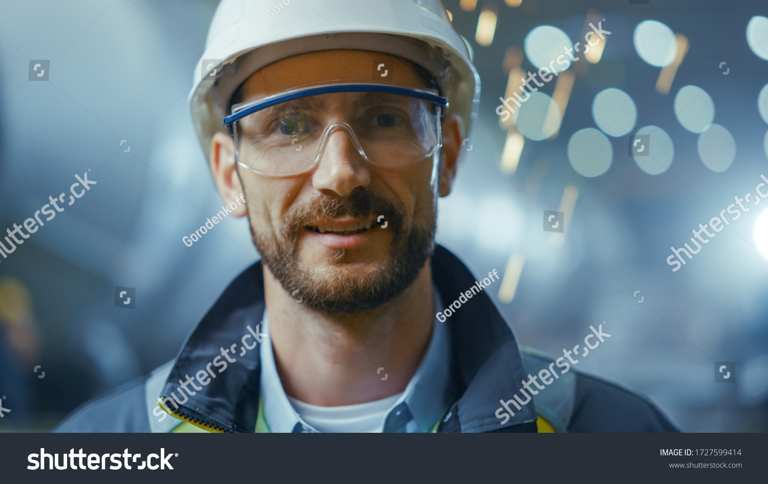 Portrait of Professional Heavy Industry Engineer / Worker Wearing Safety Uniform, Goggles and Hard Hat Smiling. In the Background Unfocused Large Industrial Factory where Welding Sparks Flying #1727599414