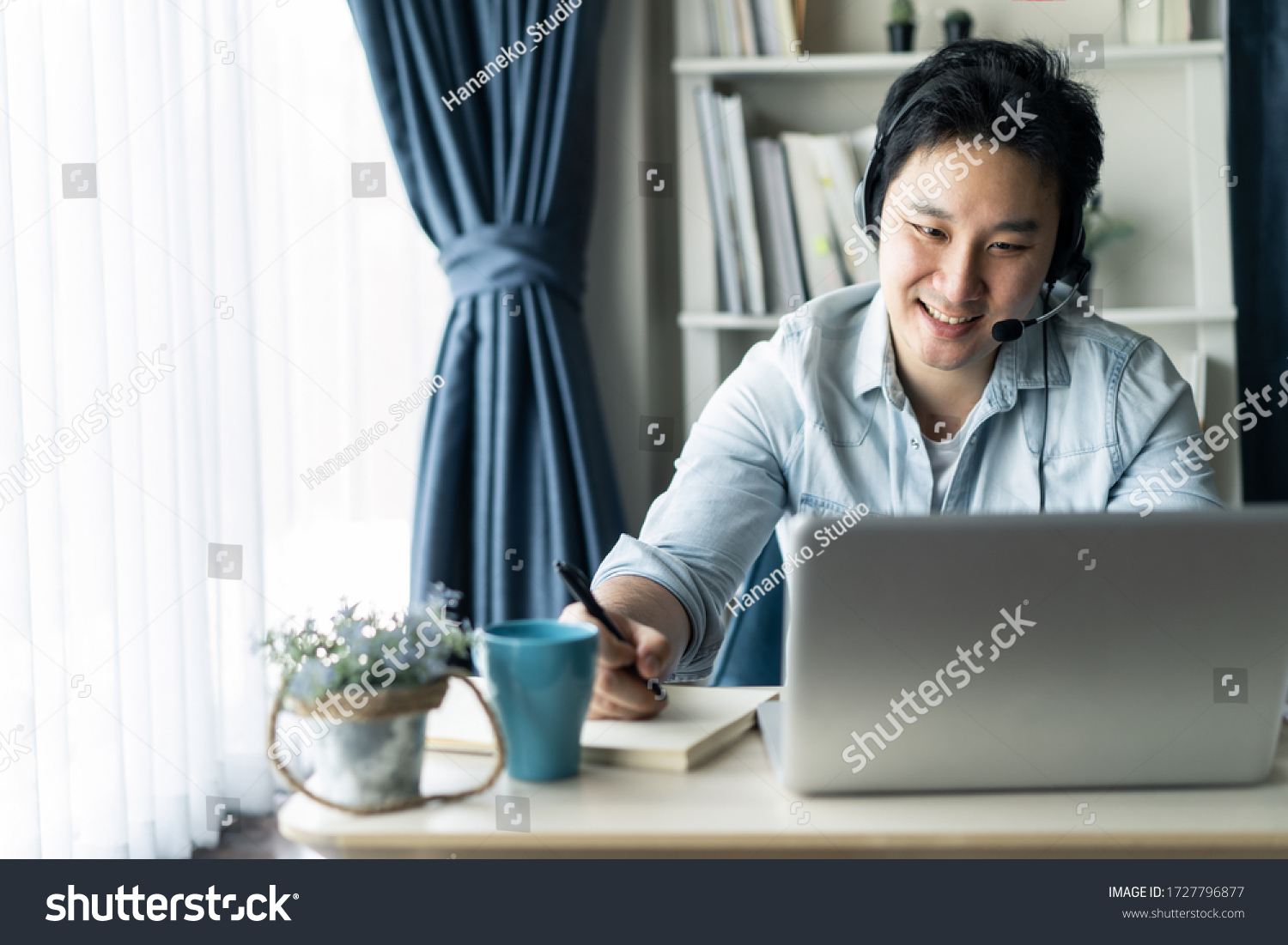 Asian businessman talking to colleague team in video call conference writing note on book with smile face. Man using computer laptop and headphone for online meeting. Smart working from home concept. #1727796877
