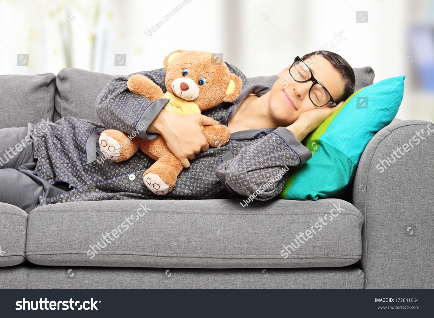 Young man holding teddy bear and taking a nap on couch at home stock photo 172841864 shutterstock - Dormire sul divano ...