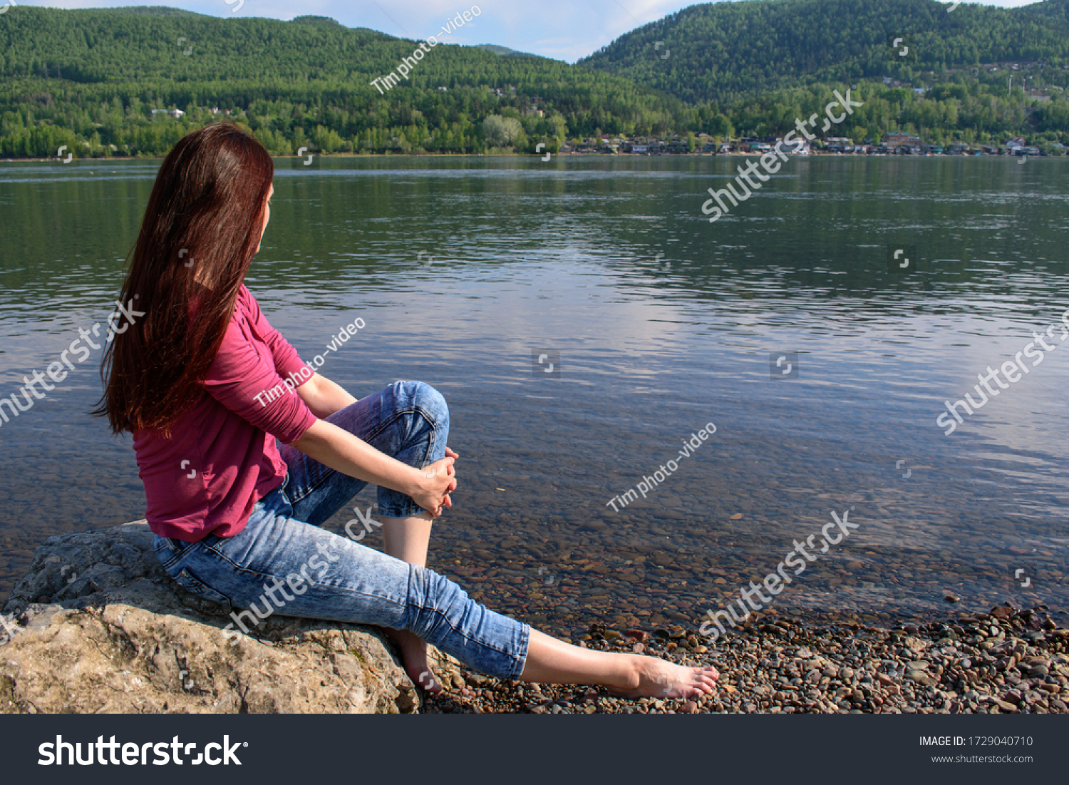 Woman on banks of a large river or lake. Long brown hair. Sits on a stone, profile view, face not visible.  Mountains, sky. Red jacket, jeans on ankle pad. Concept of summer vacation, thoughtfulness.