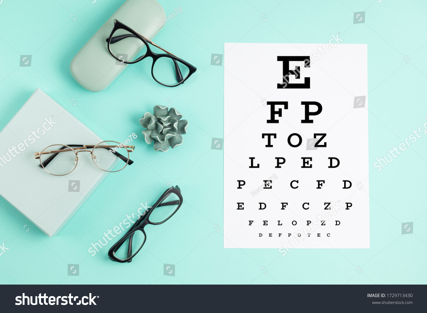Collection of eyeglasses with eye test table. Optical store, glasses selection, eye test, vision examination at optician, fashion accessories concept. Top view, flat lay #1729713430