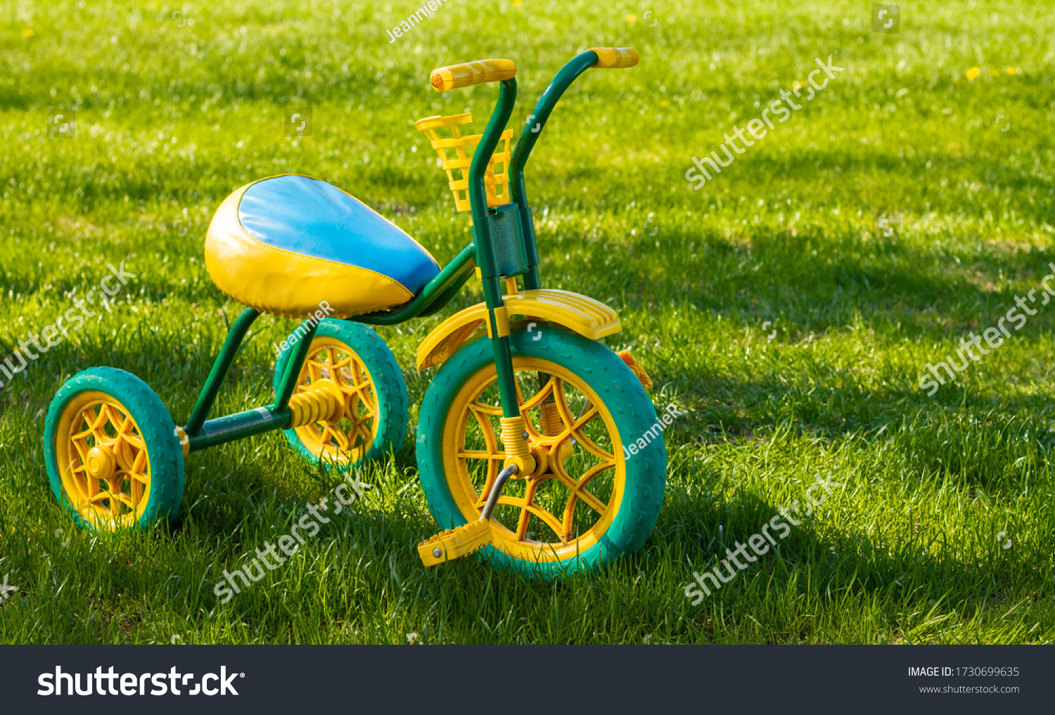 Small yellow and green children's tricycle standing on the grass on a sunny day. Copy space