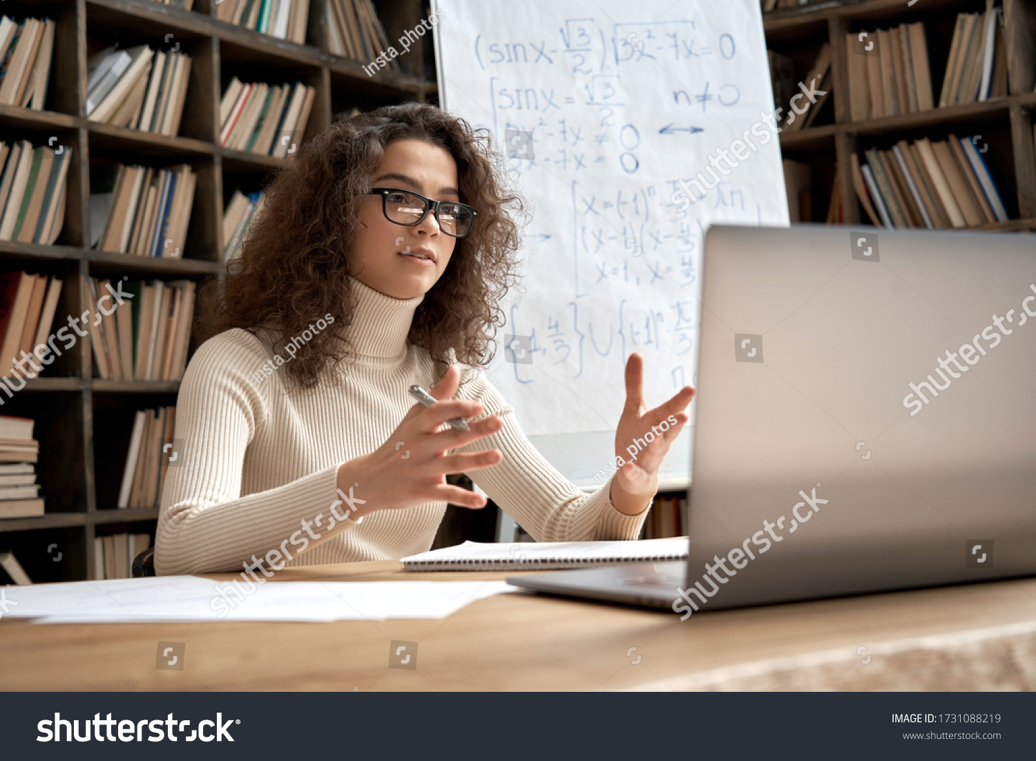 Female young hispanic school math teacher, college tutor coach looking at webcam and talking in classroom giving virtual teaching remote class online lesson by zoom conference call on laptop computer. #1731088219