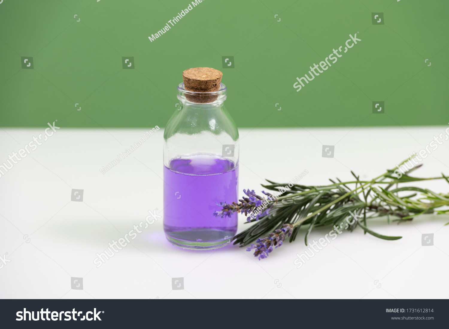 Glass jar with essential oil and lavender flowers