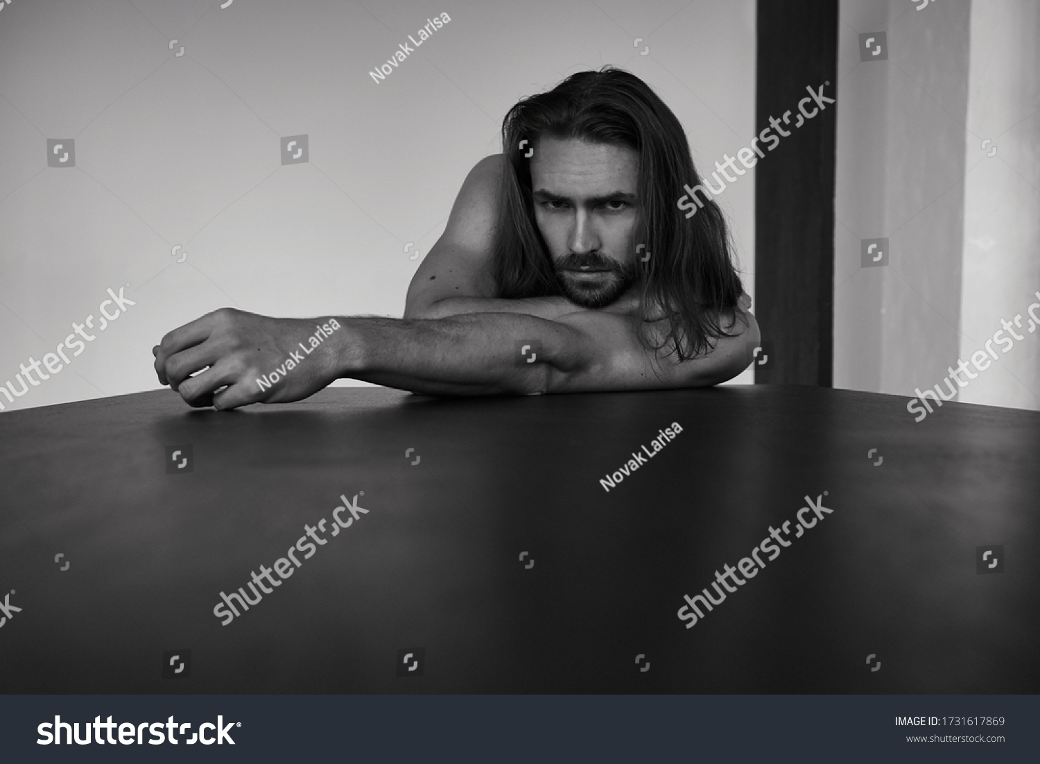 Handsome brutal man with beard and cool long hair.Sexy topless athletic body. Confident, attractive, stylish. Fashion shooting. Actor. Black and white #1731617869