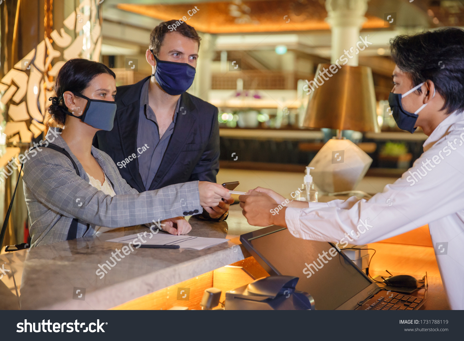 Couple and receptionist at counter in hotel wearing medical masks as precaution against virus. Young couple on a business trip doing check-in at the hotel #1731788119