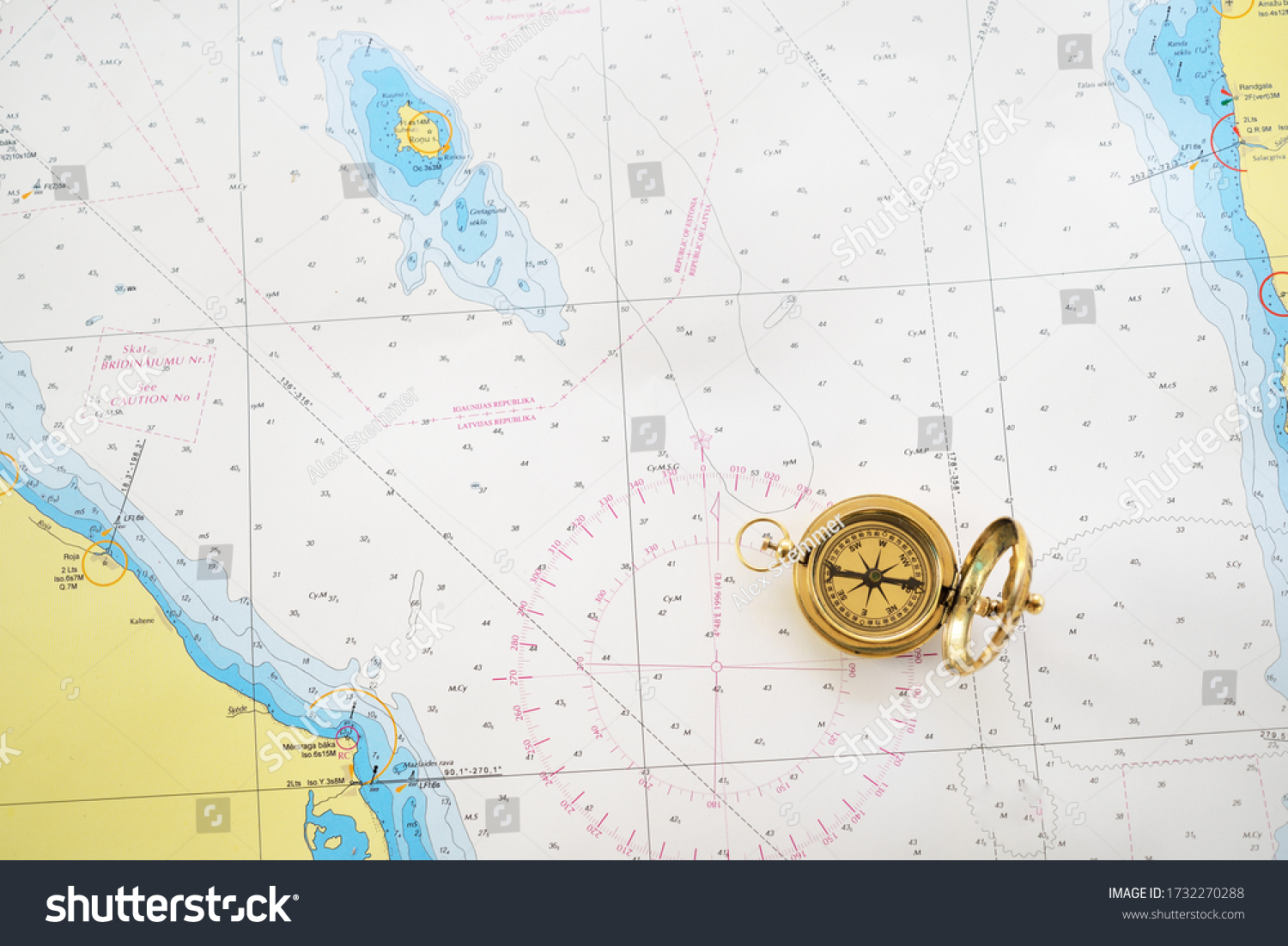Retro styled golden compass (sundial) and old white nautical chart close-up. Vintage still life. Sailing accessories. Travel and navigation theme #1732270288