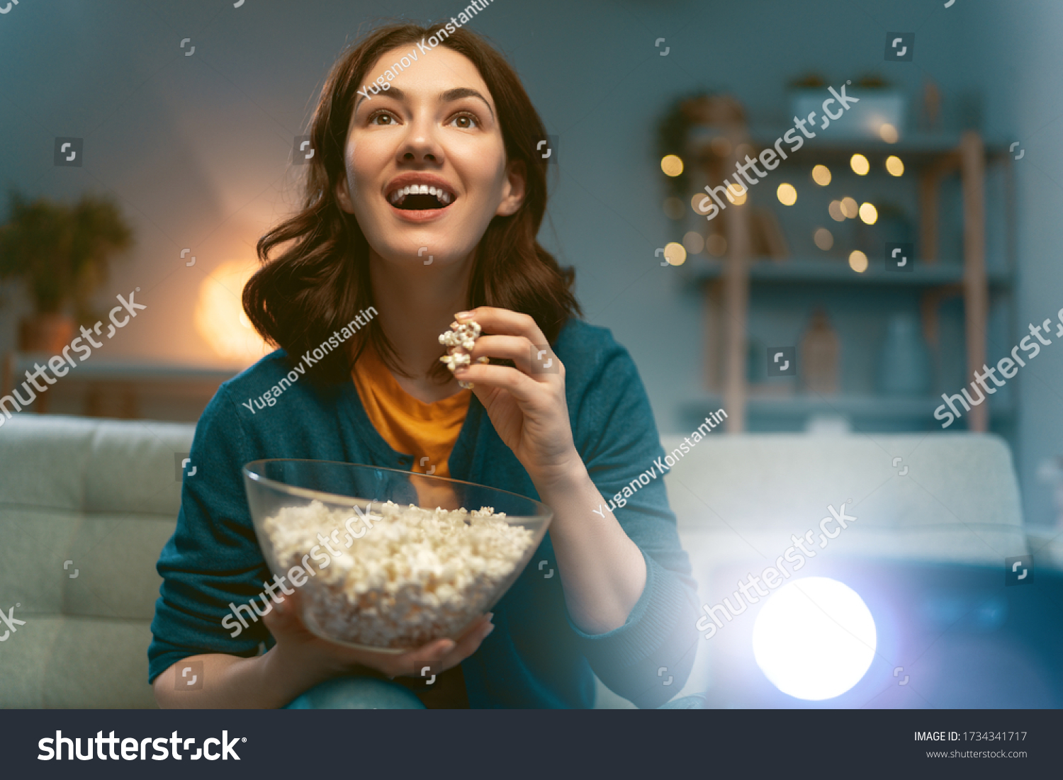 Young woman watching projector, TV, movies with popcorn in the evening. Girl spending time at home. #1734341717