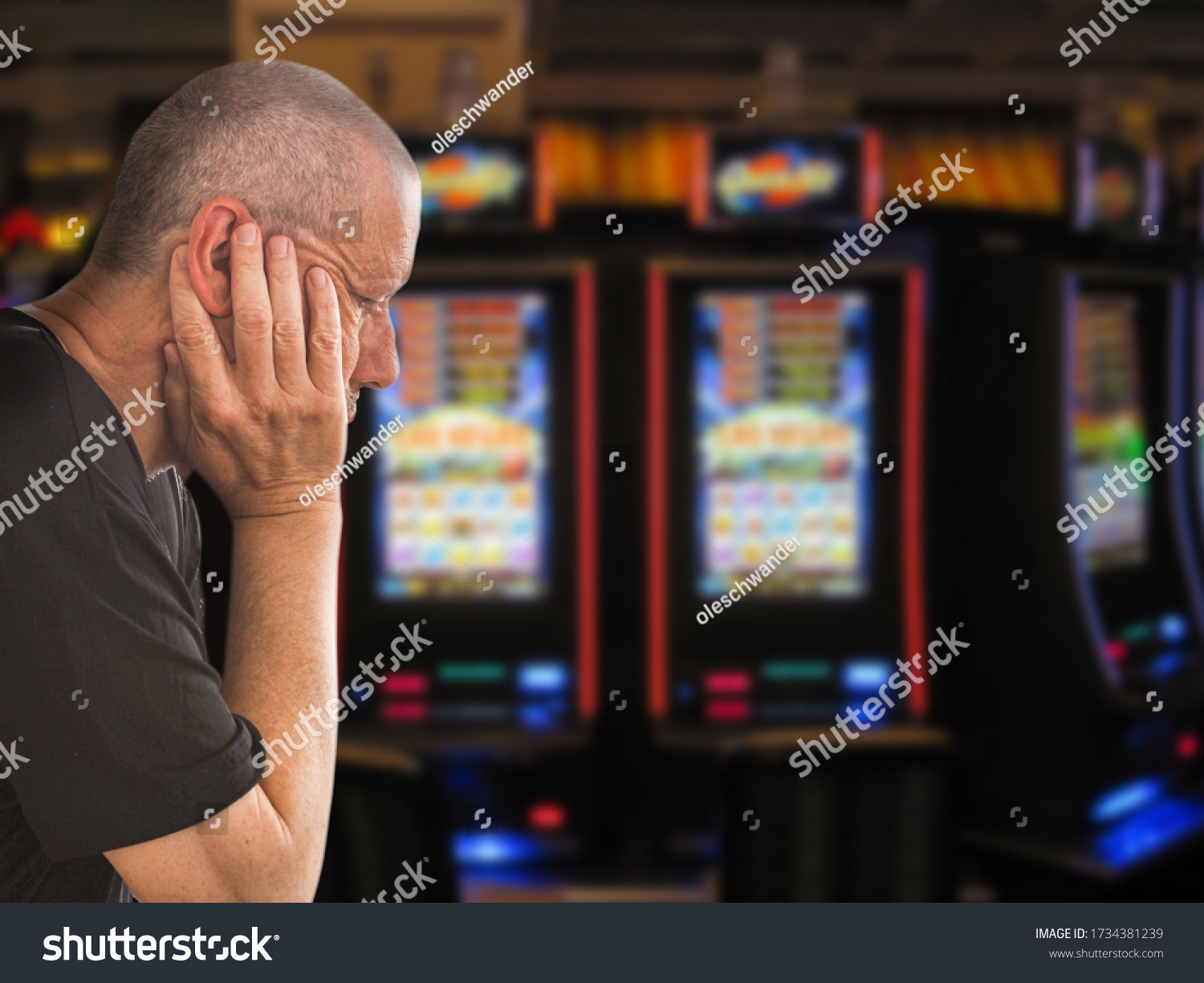 Sad and depressed caucasian man sitting with his hands on his head in front of rows of casino slot machines. Gambling addiction theme image.  Close up portrait. #1734381239