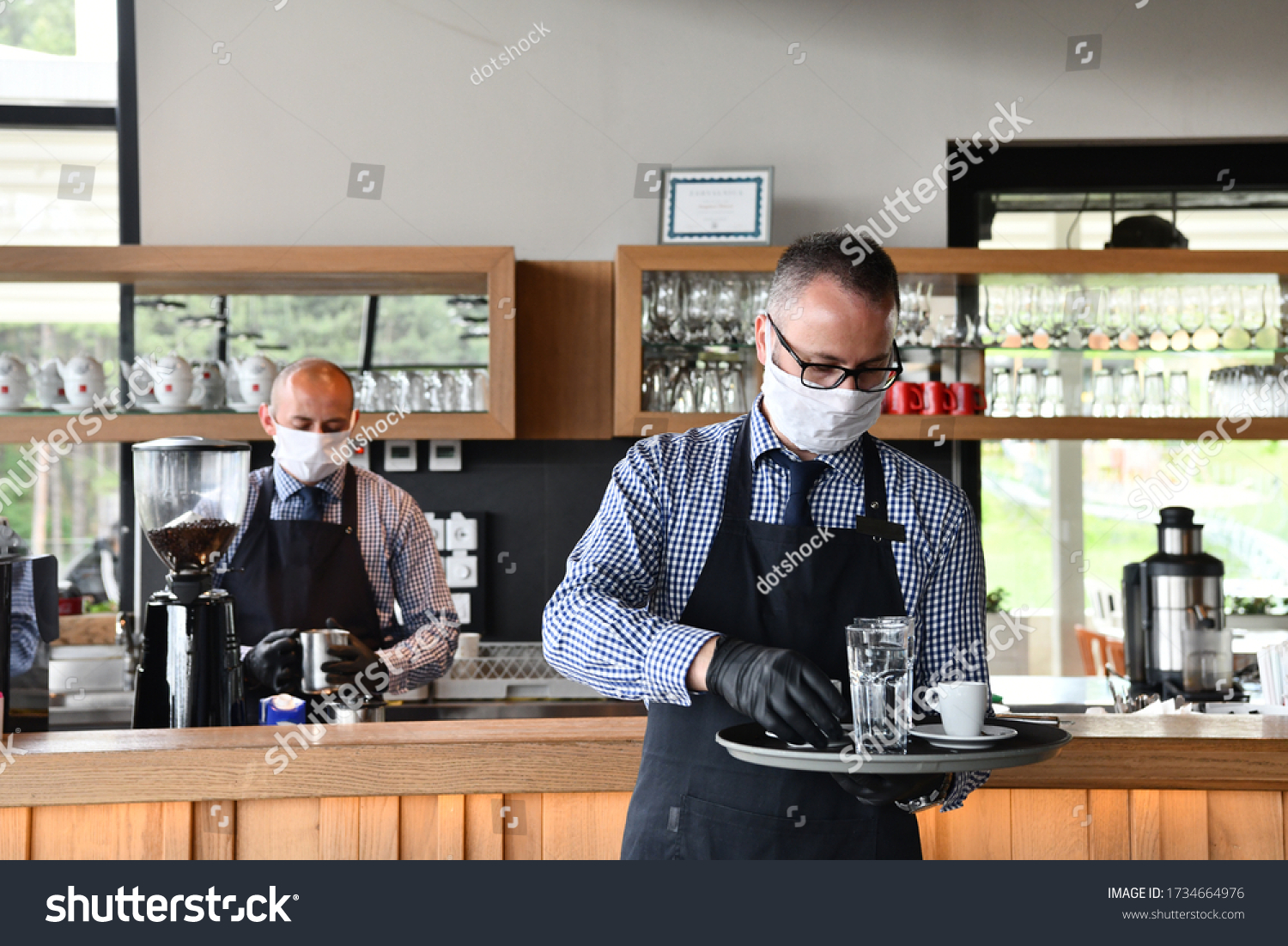 waiter in a medical protective mask serves  the coffee in restaurant durin coronavirus pandemic representing new normal concept #1734664976