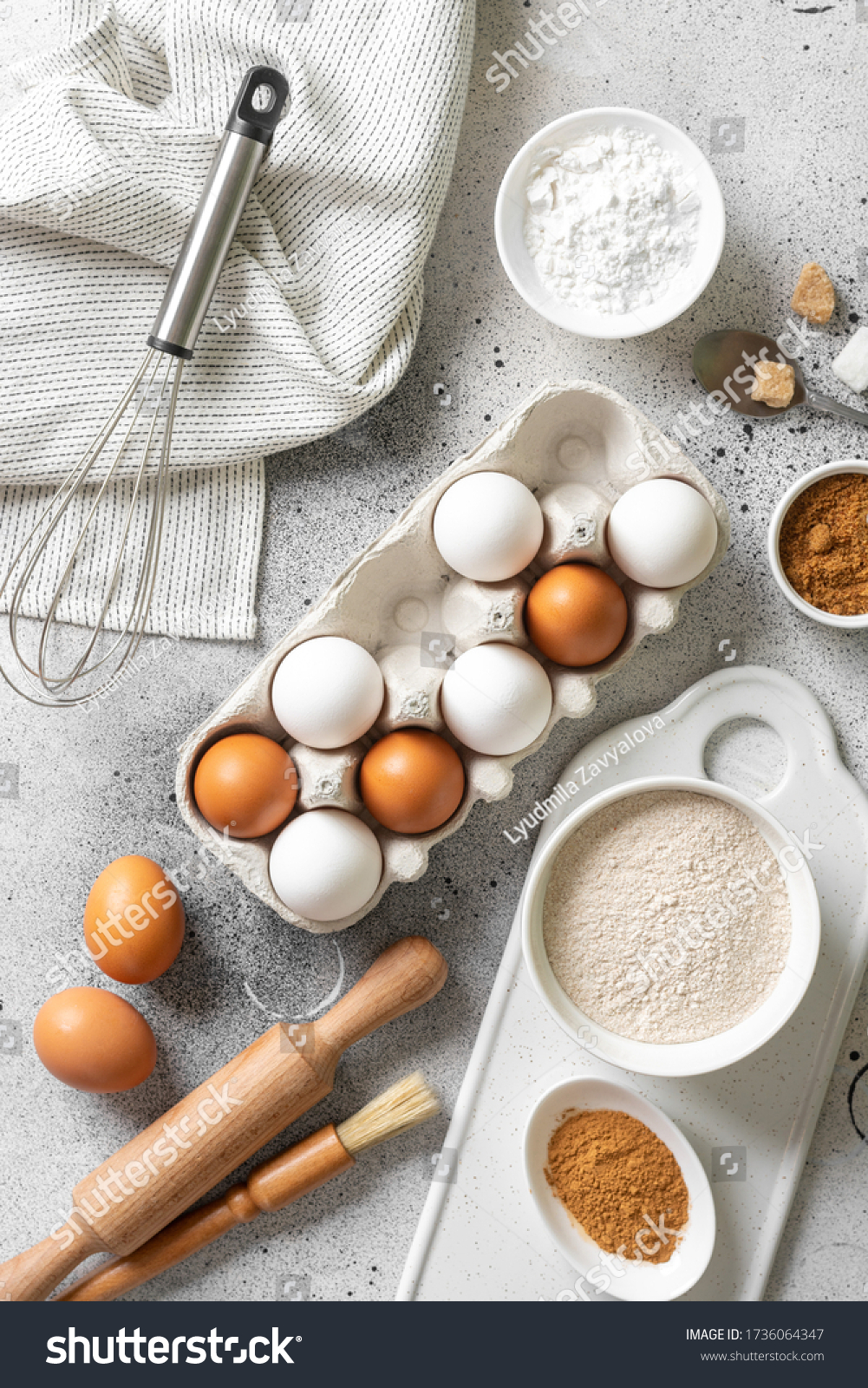 Ingredients for baking on a culinary background. Eggs, flour, cinnamon, sugar, soda on the kitchen table. Concept of preparation for baking. Top view with space for text #1736064347