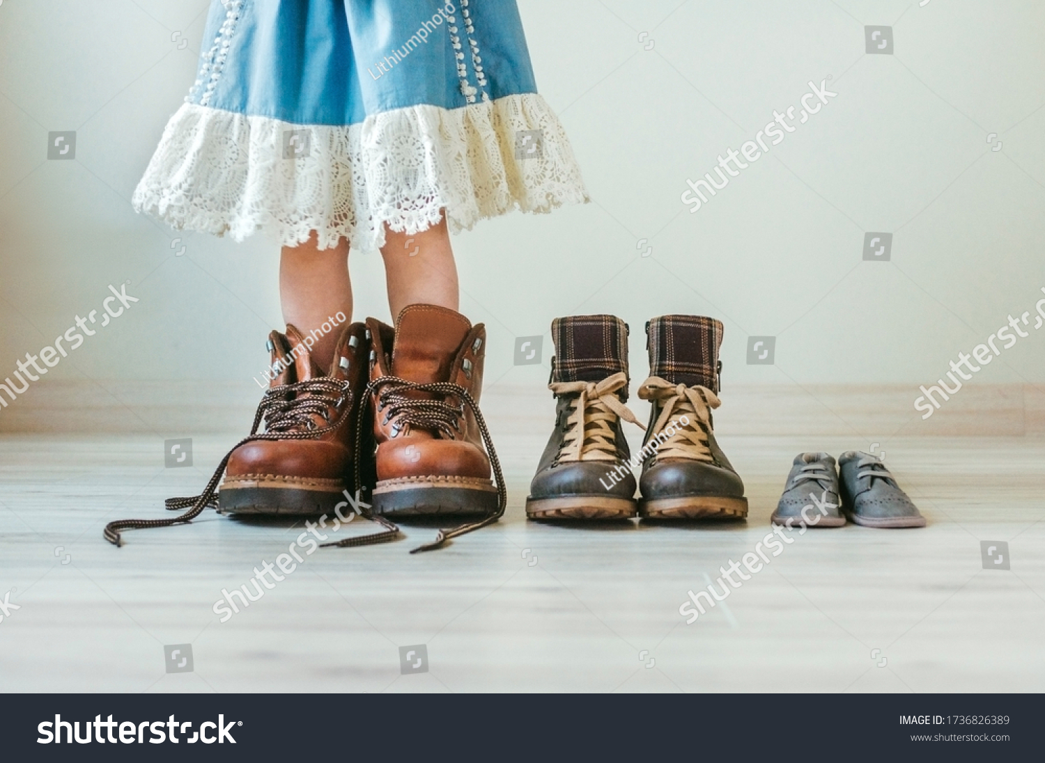 Close up of little girl putting on fathers hiking shoes. Three pairs of shoes for family indoor. #1736826389