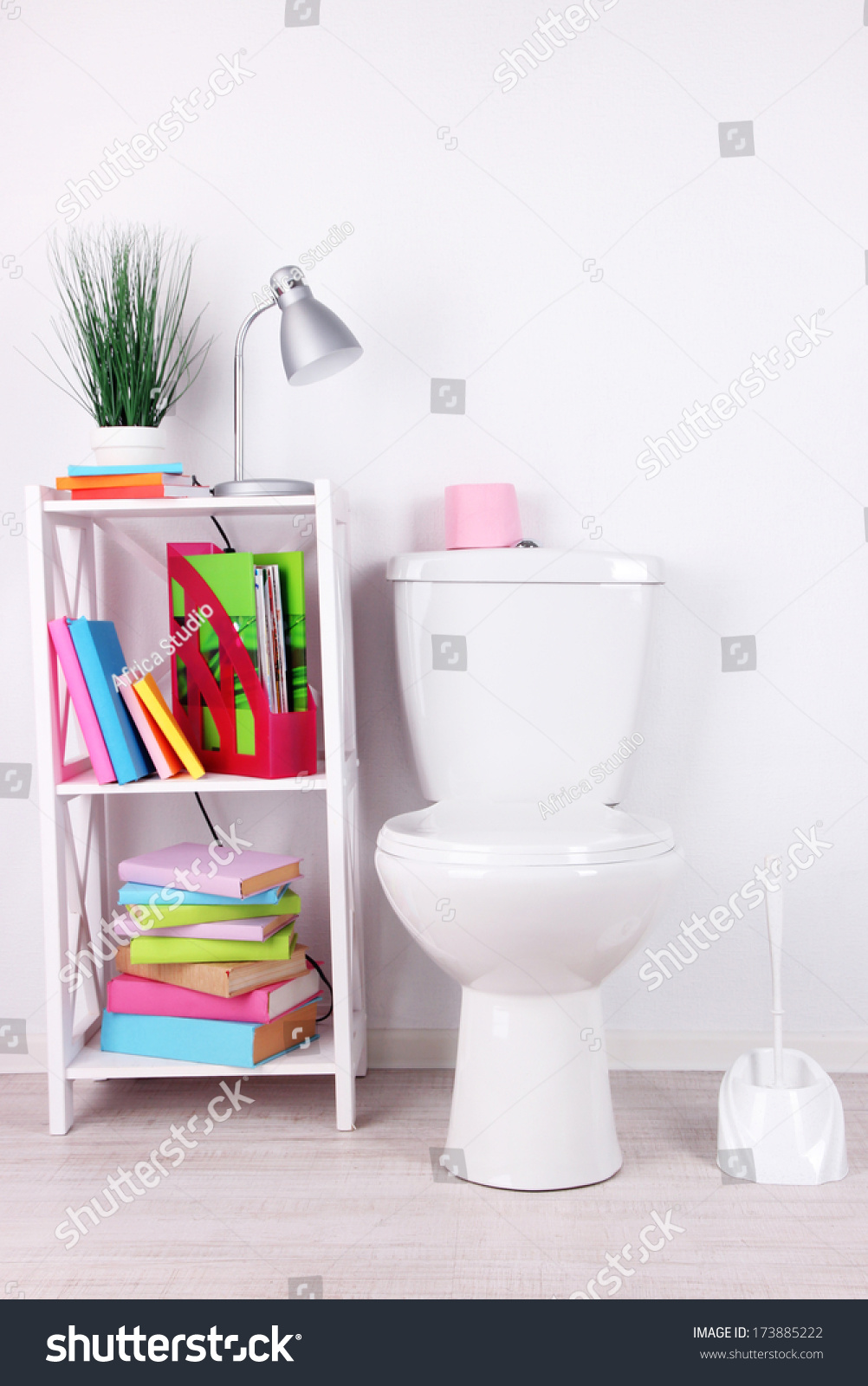 White toilet bowl and stand with books, on color wall background ...