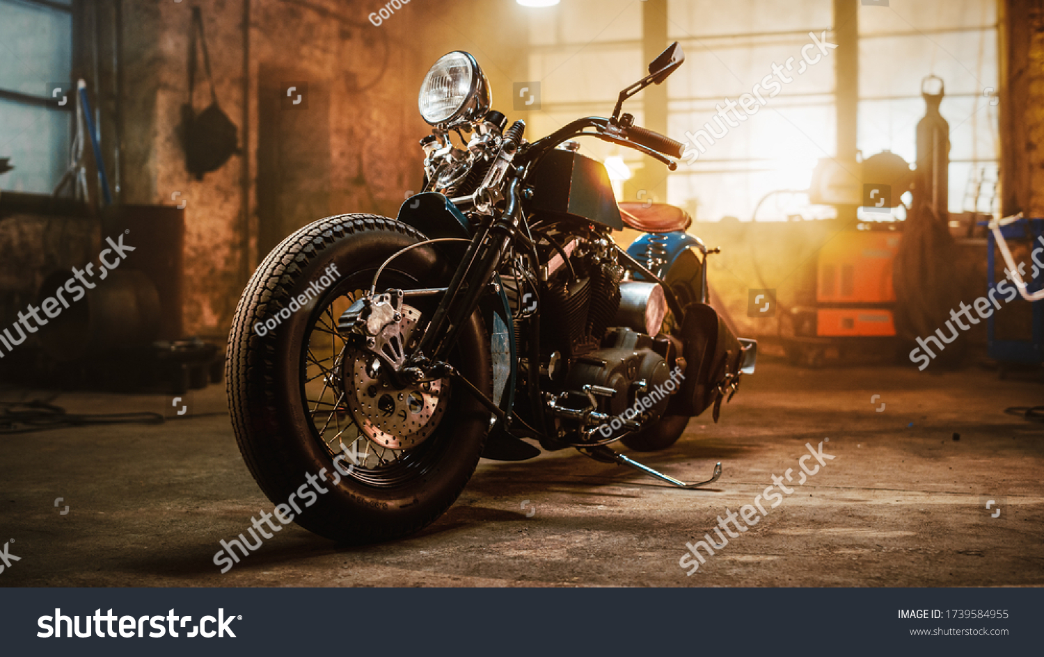 Custom Bobber Motorbike Standing in an Authentic Creative Workshop. Vintage Style Motorcycle Under Warm Lamp Light in a Garage. #1739584955