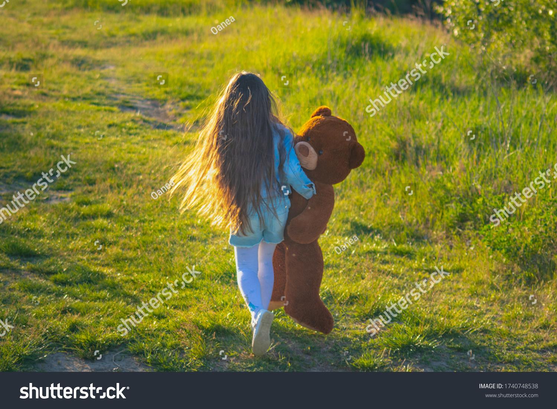 Lovely little girl with long hair and teddy bear