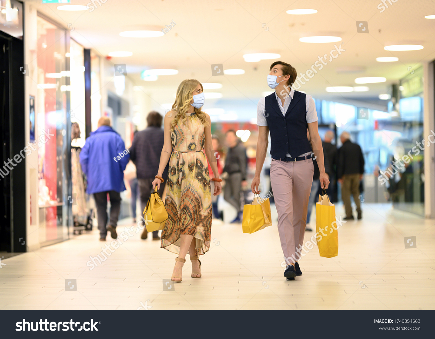 Shopping at the time of Corona Virus. Handsome young and fashion couple at the shop center walking with protective surgical face mask, shopping bags in hand and looking at shop windows. Alert Covid-19 #1740854663