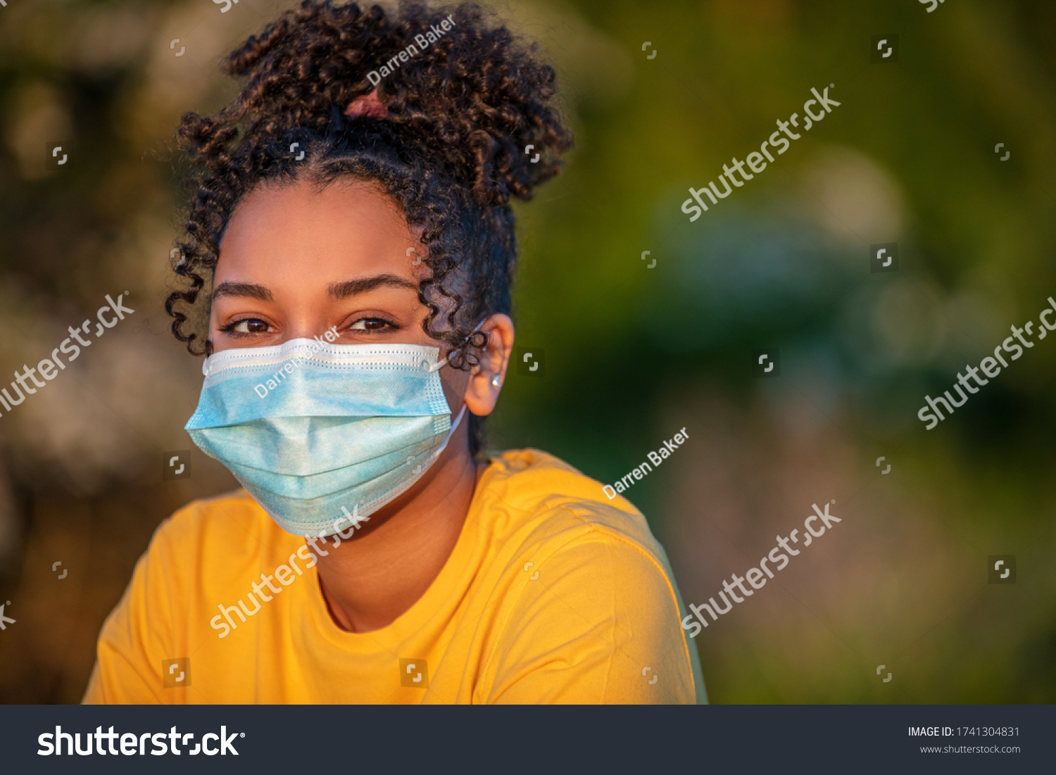 Mixed race African American teenager teen girl young woman wearing a face mask outside during the Coronavirus COVID-19 virus pandemic