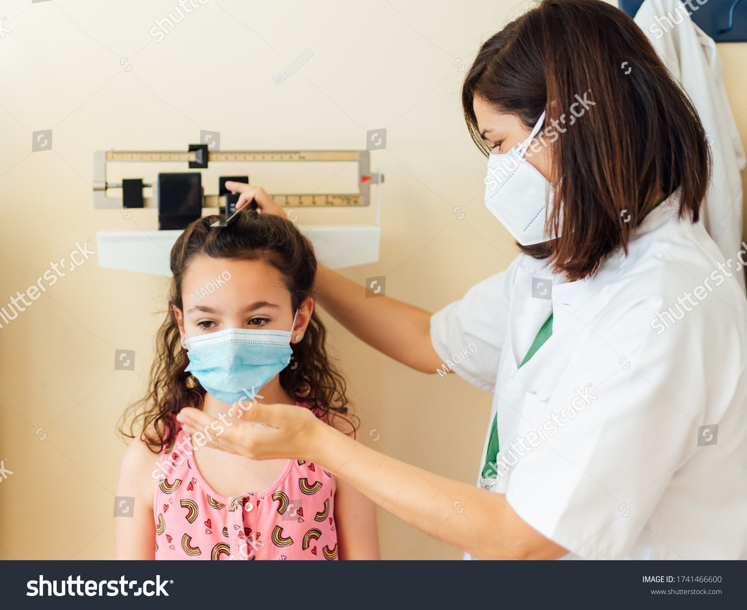 The pediatric doctor measures and weighs the child in the clinic office. They both wear a mask to protect against the covid-19 virus. The young girl is examined in the hospital to see how she is growi #1741466600