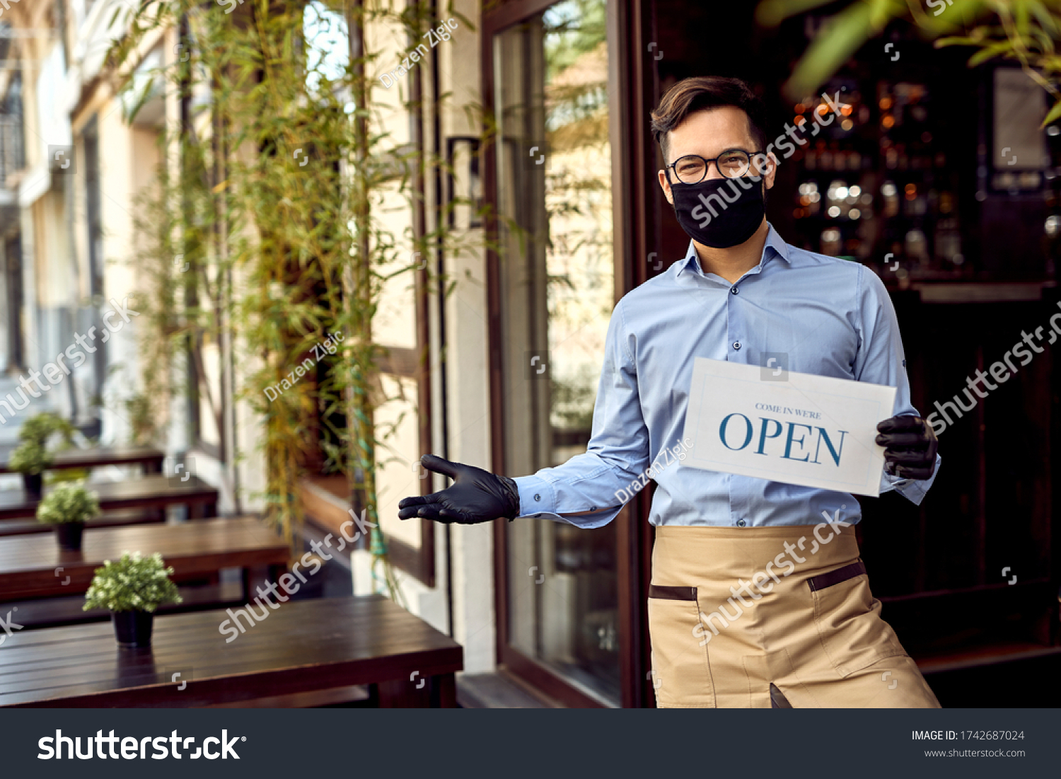 Happy waiter with protective face mask holding open sign while standing at cafe doorway.  #1742687024