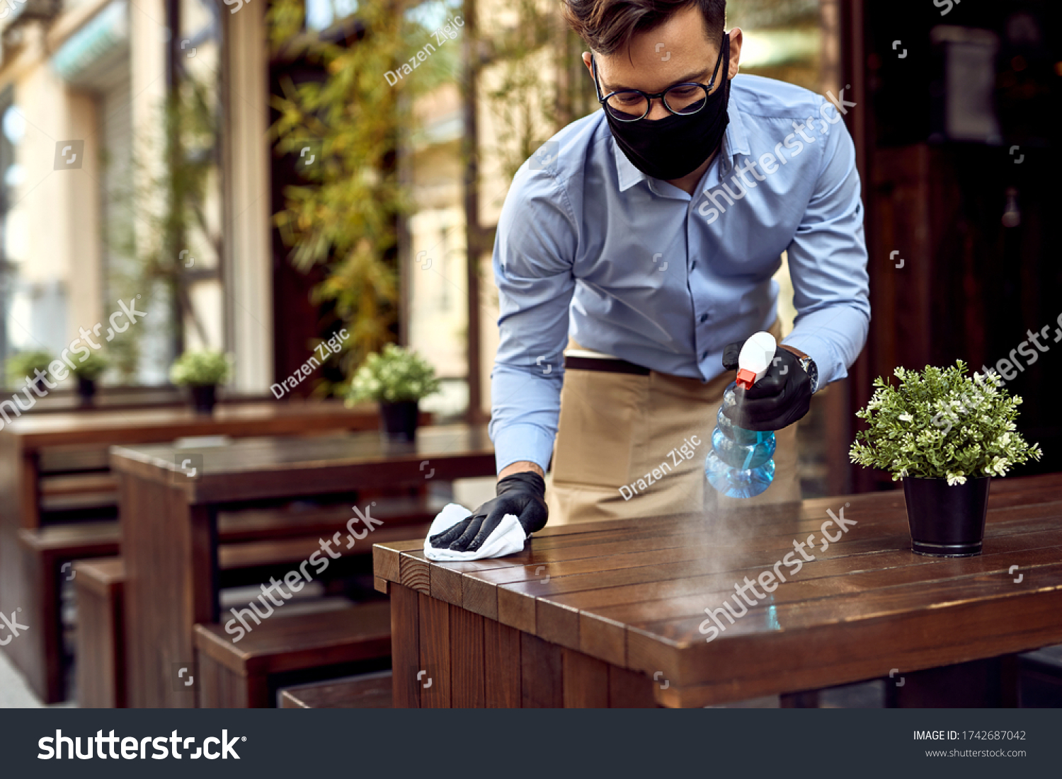 Waiter wearing protective face mask while disinfecting tables at outdoor cafe. #1742687042
