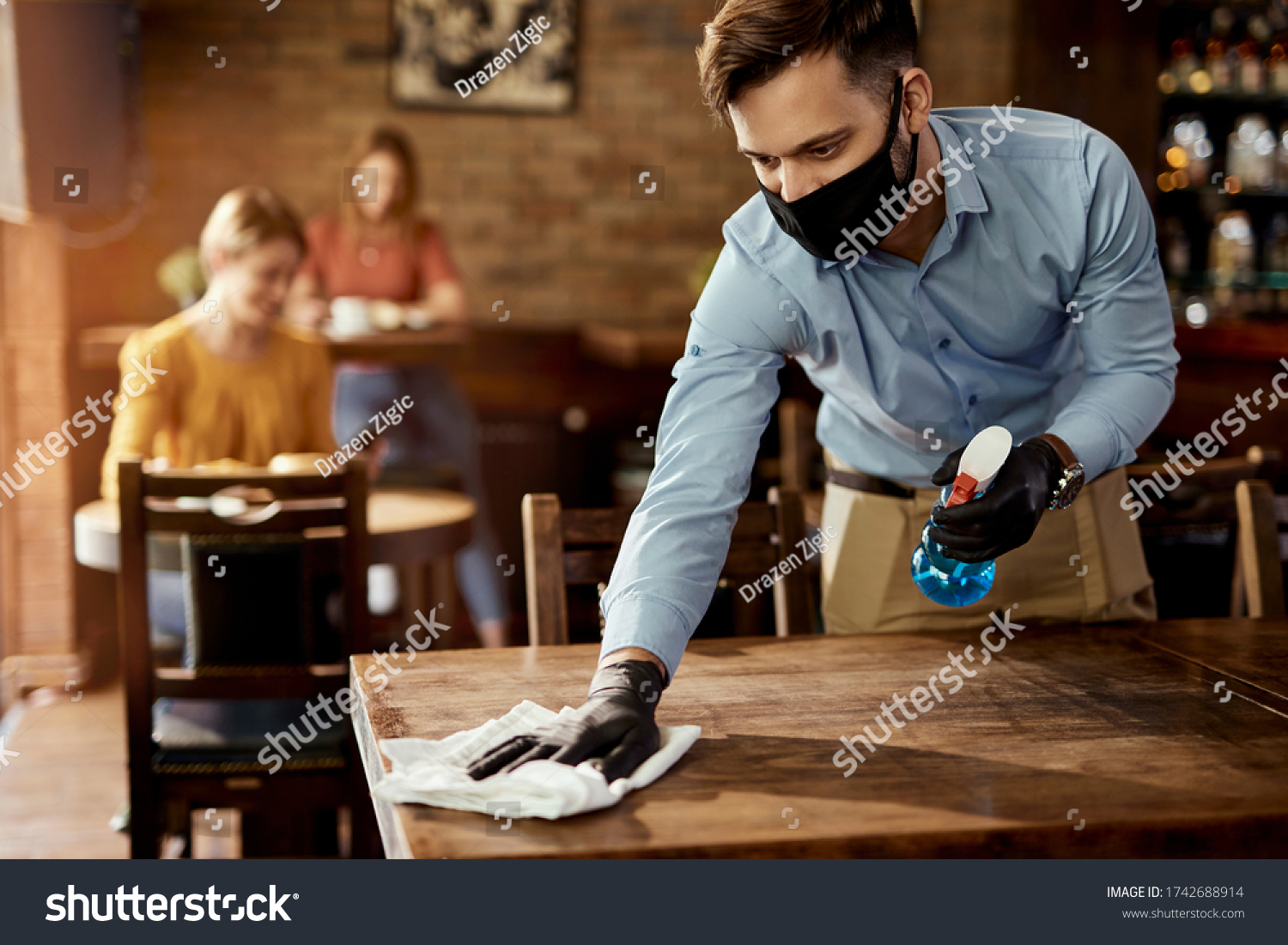 Young waiter wearing protective face mask while cleaning tables while working in a cafe.  #1742688914