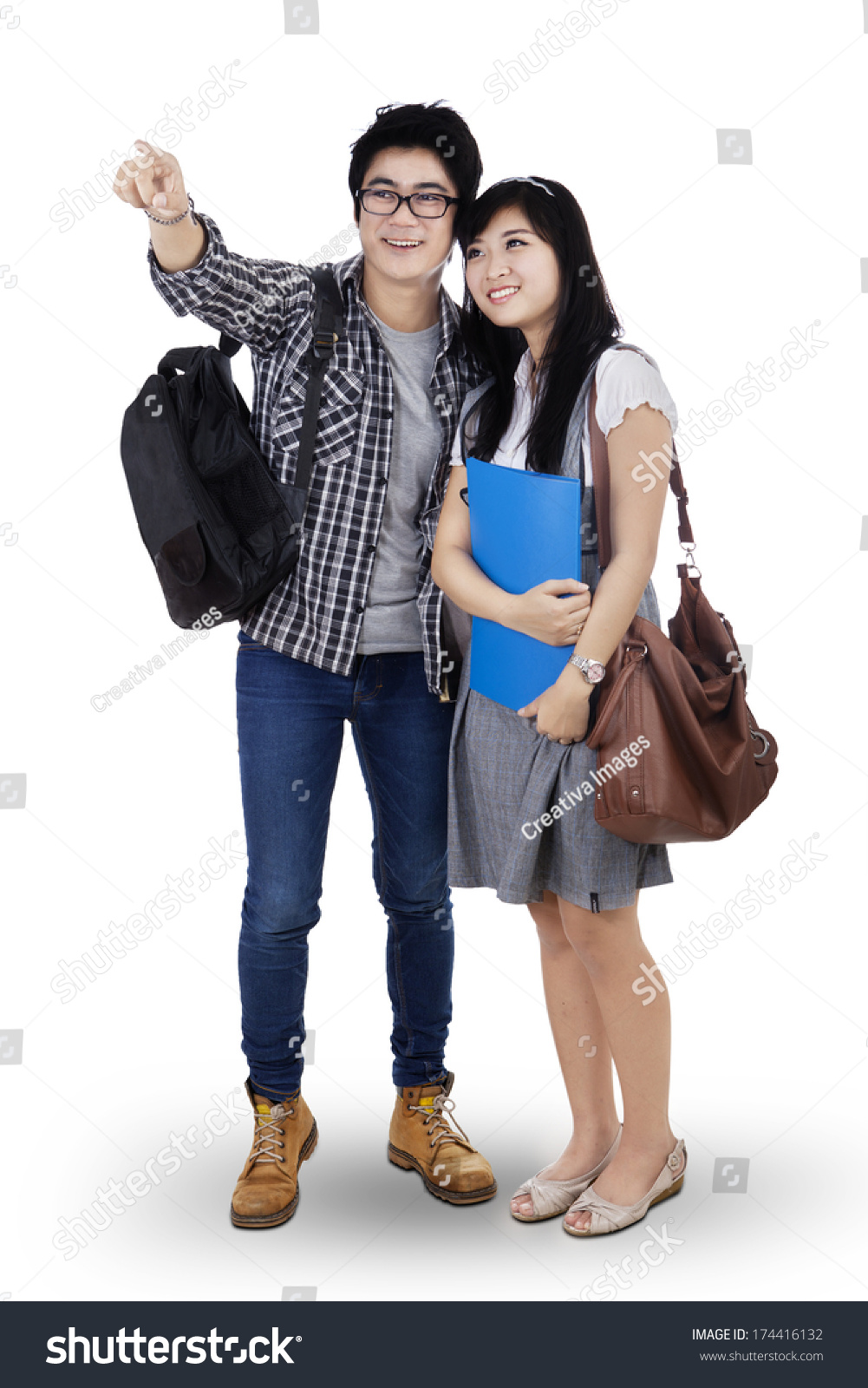 Happy Trendy College Students With Bags And Books Pointing At Copy Space