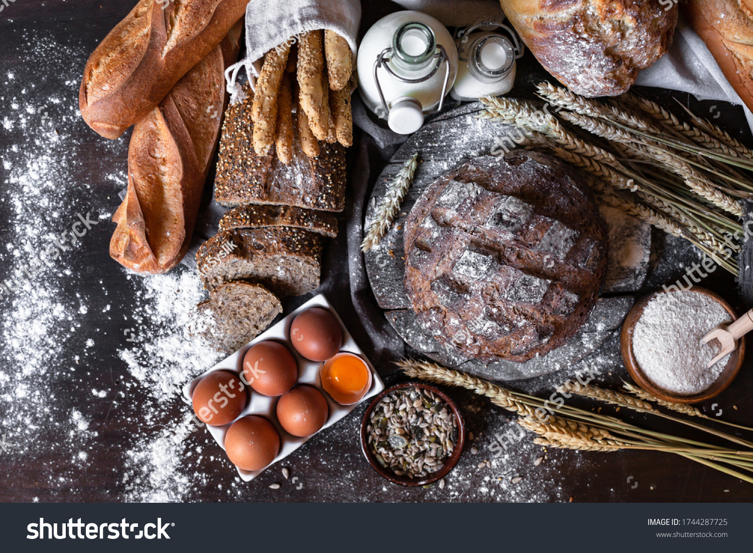Concept of homemade bread, natural farm products, domestic production. Healthy and tasty organic food. Freshly baked round whole grain bread. Top view flat lay, dark black background.
