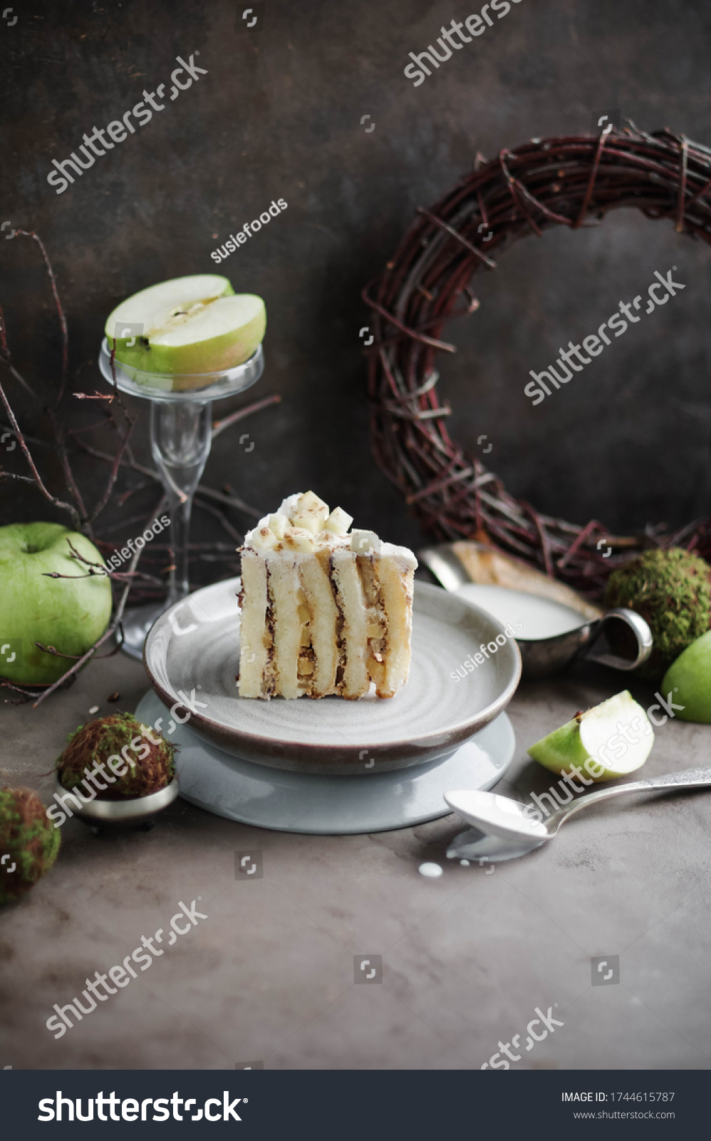 Slice of vertical biscuit cake with apple filling on a plate. Autumn desserts.  #1744615787