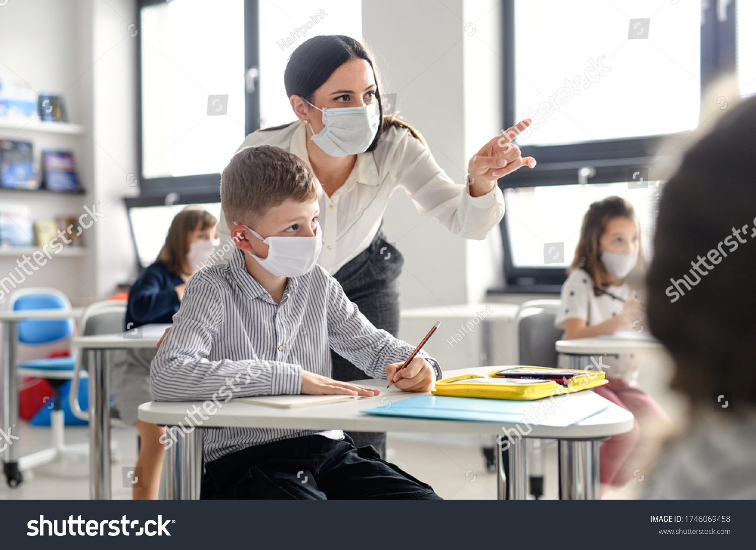 Teacher and children with face mask back at school after covid-19 quarantine and lockdown. #1746069458
