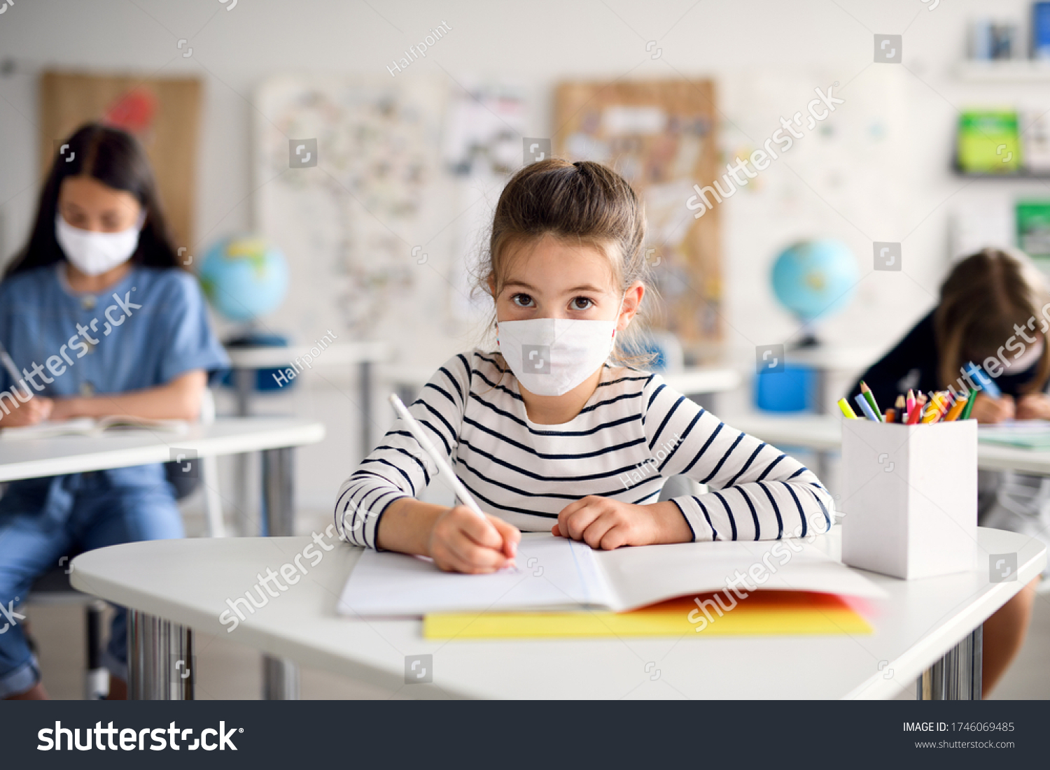 Child with face mask back at school after covid-19 quarantine and lockdown, writing. #1746069485