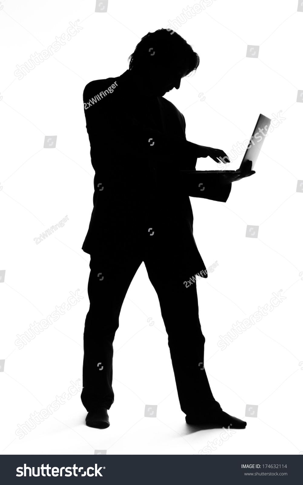 Silhouette Of A Man In Suit Typing On A Laptop Stock Photo ...