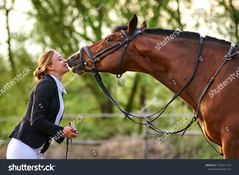 Horse rider girl and horse on a farm. horse kisses a girl. #1746321722