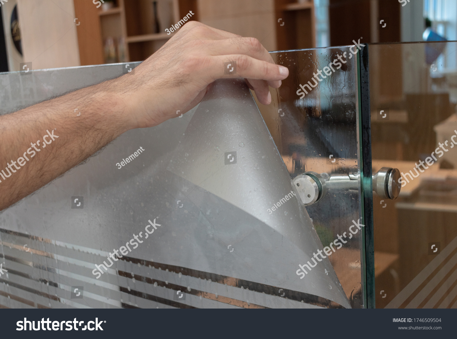 Frosted window film application detail close-up. Skilled men's hand #1746509504