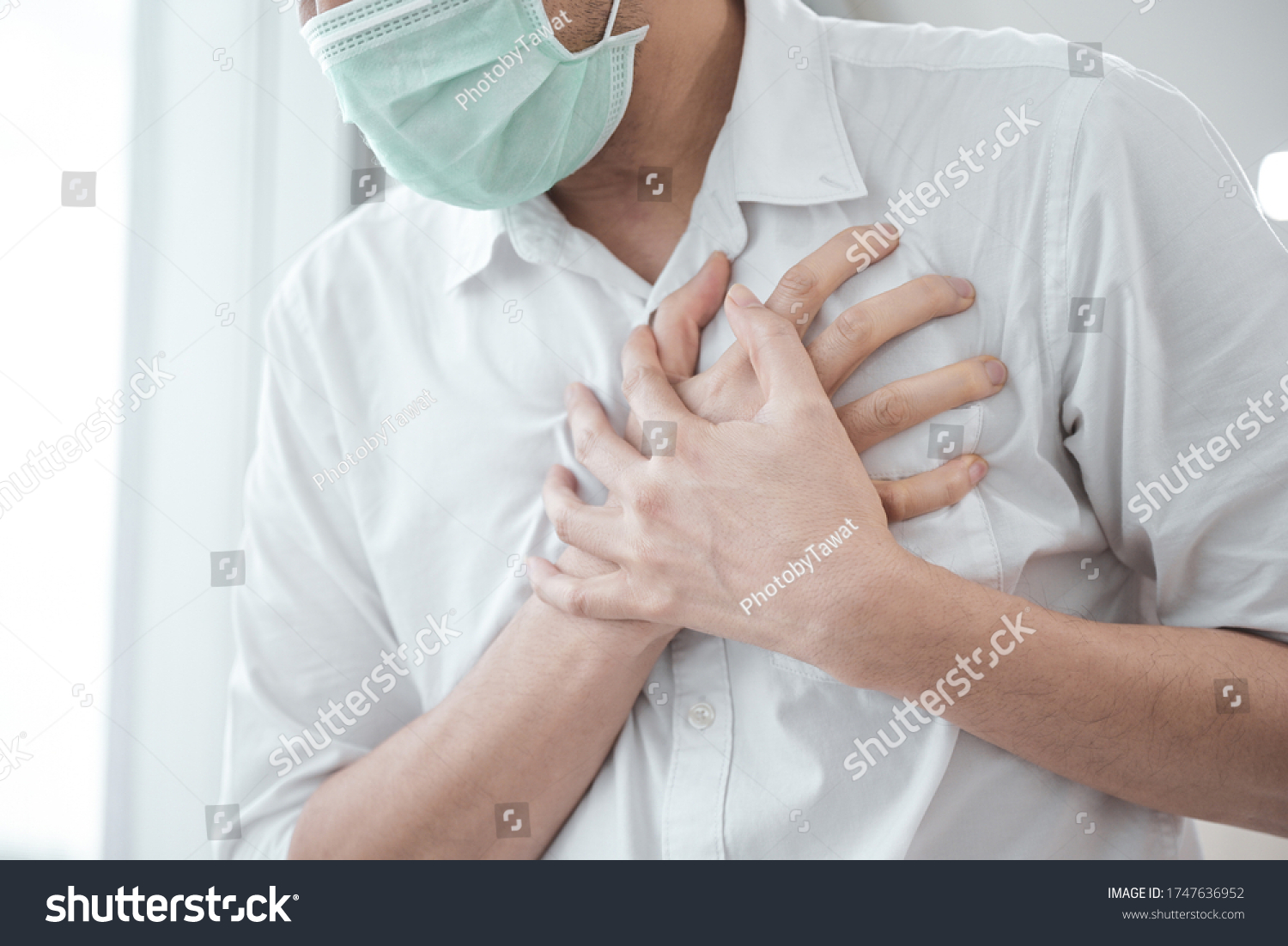 Man wear medical face mask, symptoms of coronavirus diseases, chest pain - heart attack, fever, cough, shortness of breath during work in office, health care concept. #1747636952
