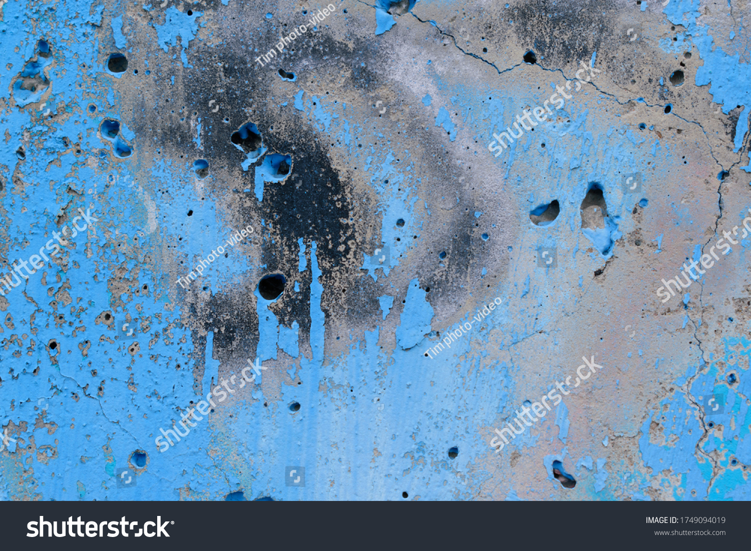 Gray concrete wall for backdrop. Old paint, color Malibu, Hue Blue. Black abstract spots, indentations and pits.