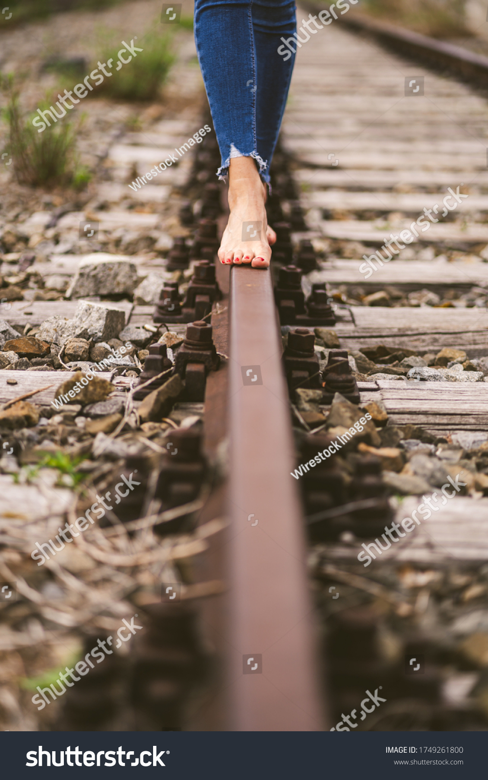 https://image.shutterstock.com/shutterstock/photos/1749261800/display_1500/stock-photo-a-vertical-shot-of-a-female-in-jeans-walking-through-the-train-rails-barefoot-1749261800.jpg